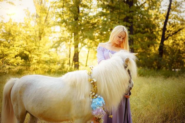 白いユニコーンの馬の夢を抱き締める紫色のドレスの女性が来る