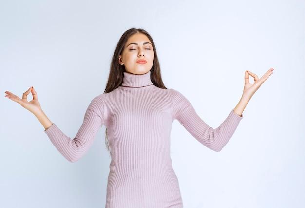 Женщина в фиолетовой рубашке делает медитацию.