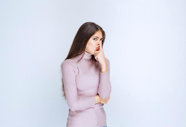 リラックスした魅力的なポーズを与える紫色のシャツの女性。
