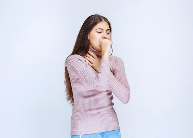 紫色のシャツを着た女性は喉が痛い。