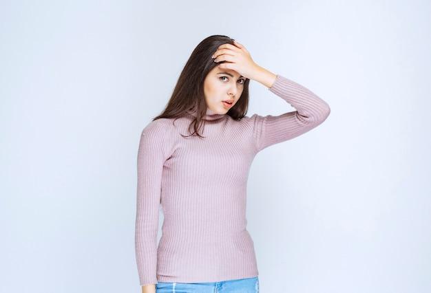 紫色のシャツを着た女性は眠い、または頭痛がします。