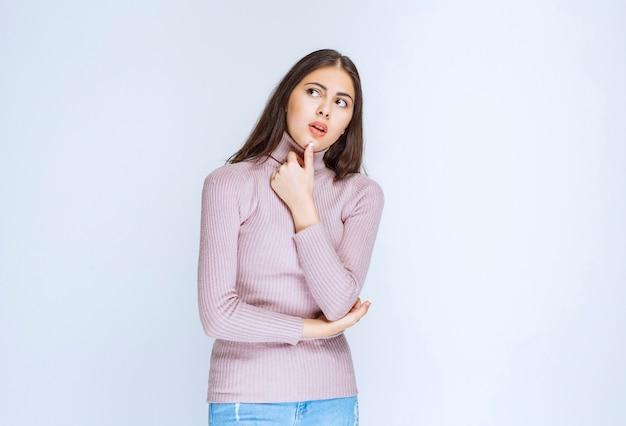 紫色のシャツを着た女性は驚きと思慮深く見えます。