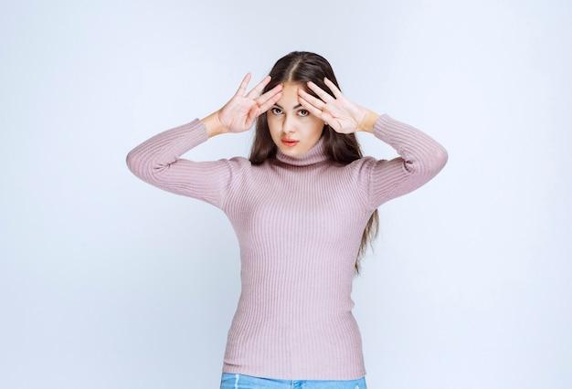 Женщина в фиолетовой рубашке выглядит напуганной или напуганной.