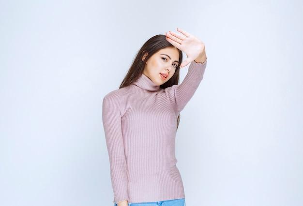 Женщина в фиолетовой рубашке, отвергая что-то руками.