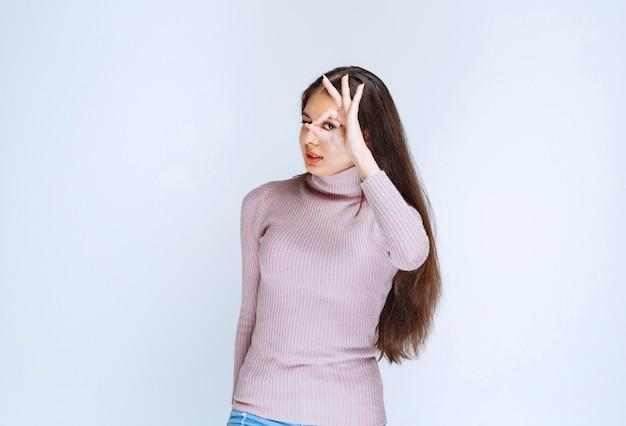 楽しみの手のサインを示す紫色のシャツの女性。