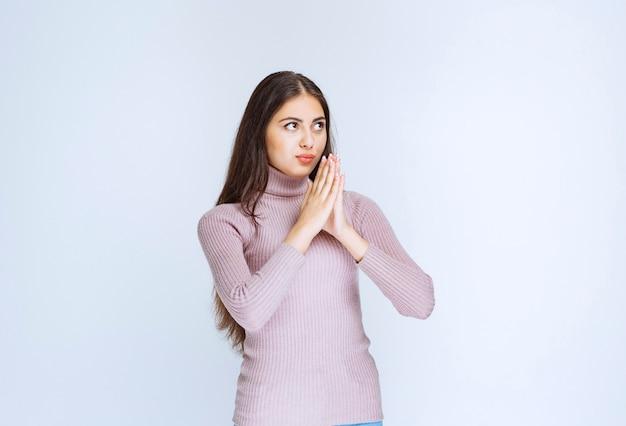 Женщина в фиолетовой рубашке объединяет руки и мечтает.