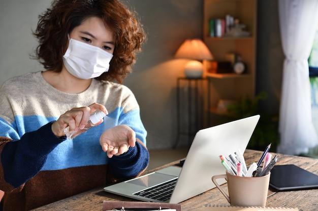 Женщина в карантинном и социальном дистанции носит хирургическую маску и моет руки спиртовым гелем-дезинфицирующим средством, работая дома во время пандемии коронавируса covid-19