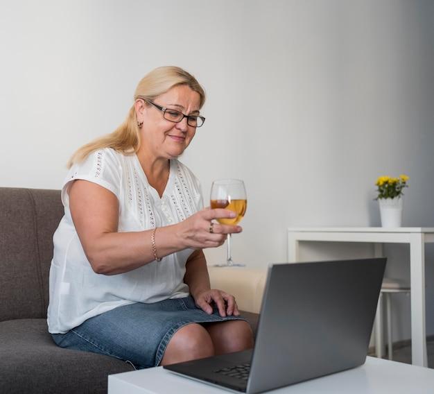 ノートパソコンで飲み物を持っている検疫の女性