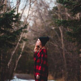 Женщина в красно-черном клетчатом пальто и черной шапочке между деревьями