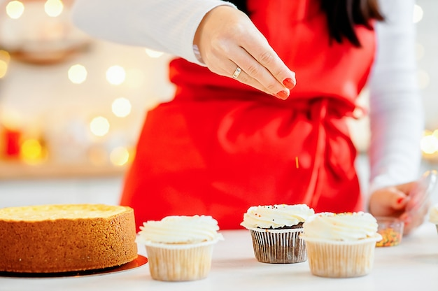 Женщина в красном фартуке украшает кексы цветной посыпкой на кухне дома. домашние десерты, приготовление и украшение капкейков