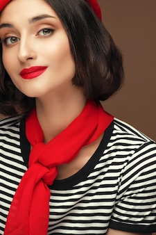베이지색 배경 위에 아름다운 짧은 머리를 가진 빨간 베레모와 스트립 티셔츠를 입은 여성 프랑스 스타일 갈색 머리