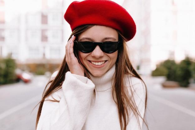 通りでポーズをとって赤いベレー帽の女性
