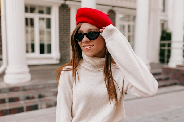 Женщина в красном берете позирует на улице