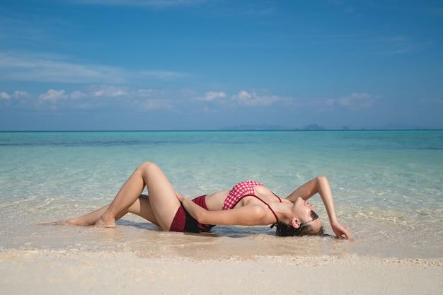 澄んだ水の砂浜に横たわっている赤いビキニ水着の女性。夏休み。