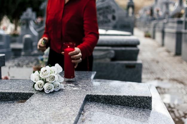 Женщина в красной блузке зажигает свечу и возлагает цветы любимому человеку на кладбище.
