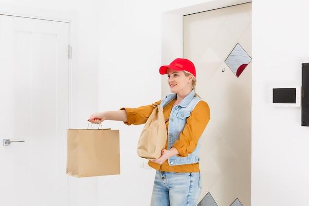 ファーストフードの注文の家の背景を与える赤い帽子の女性。食品と紙のパケットを保持している女性の宅配便。ショップやレストランから自宅への商品配送。コピースペース