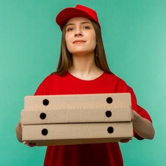 Женщина в красной кепке, футболке дает коробки для пиццы заказ еды на синем.