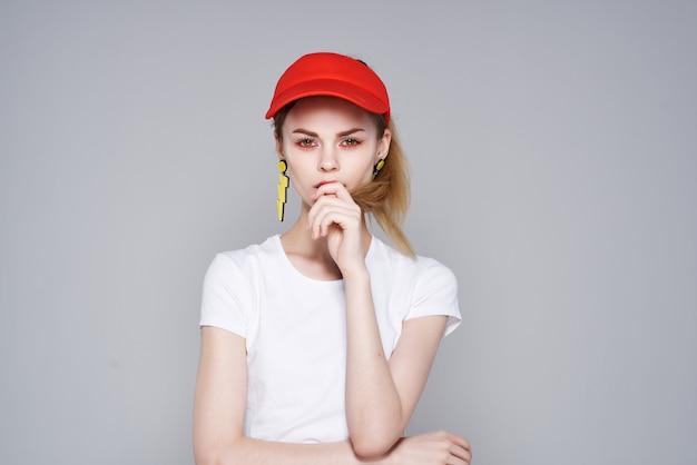 Женщина в красной шапочке желтые серьги гламур летней моды. фото высокого качества