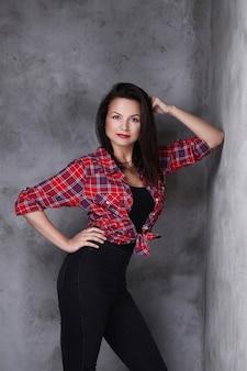 赤いチェックのシャツと黒のジーンズの女