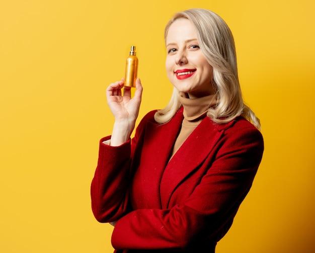 Женщина в красном пальто с духами на желтой стене