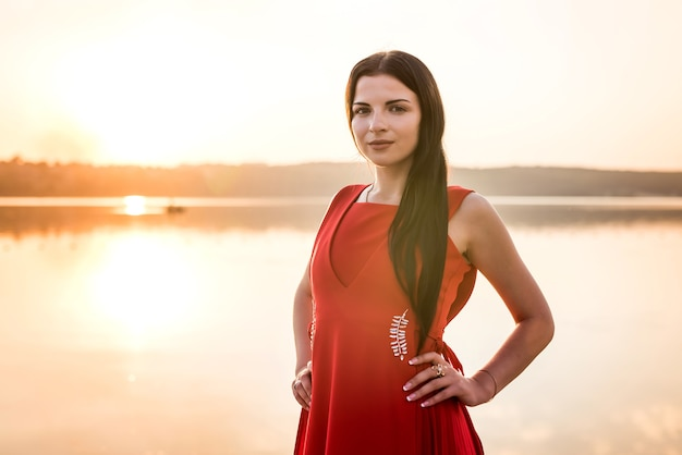 湖の夕日に対して赤いドレスを着た女性
