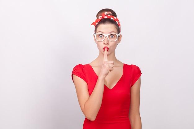 秘密のサインを示す赤いドレスとドットのbandgeの女性