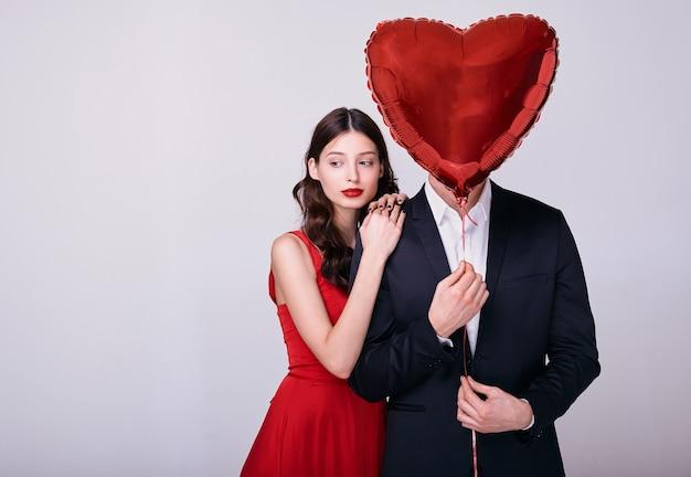 赤いドレスを着た女性とスーツを着た男性は、白い背景の上の彼の顔に赤いハート型の風船を保持します。