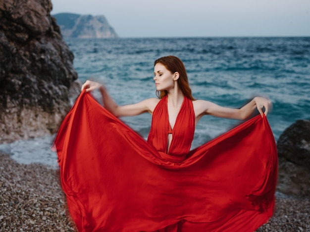 贅沢なポーズをとる海の岩のそばに赤いドレスを着た女性