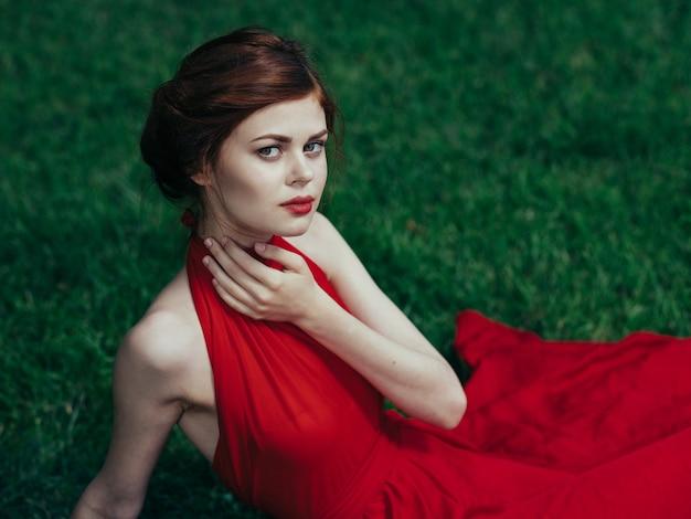 Женщина в красном платье зеленая трава парк роскошный шарм модель