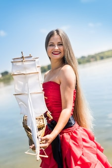 ビーチでボートモデルを保持している赤いドレスの女性