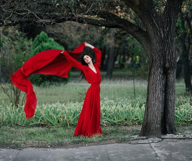 森の魅力の豪華な木の赤いドレスの女性