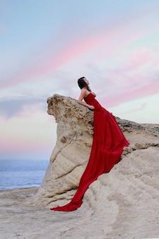 Женщина в красном платье с длинным шлейфом рядом с морем.
