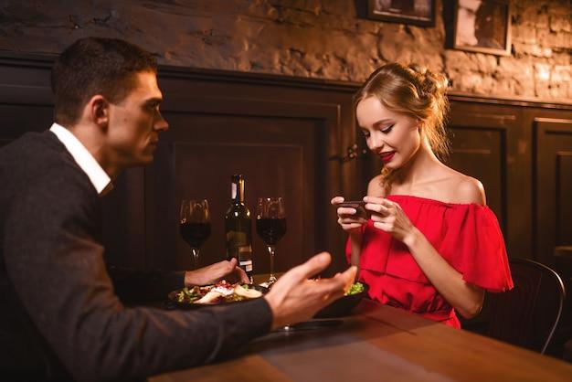 빨간 드레스에 여자는 전화에 그녀의 남자의 이미지를 만드는