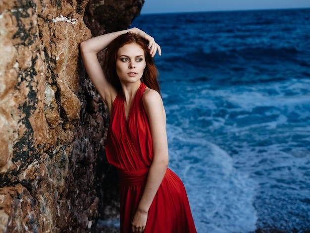 ロッキー山脈の海をポーズする赤いドレスの女性