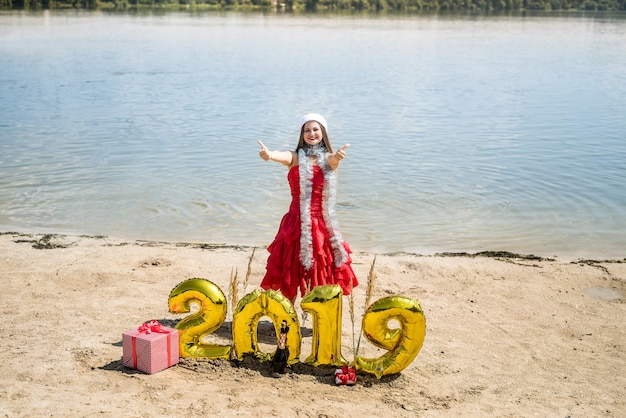 新年の装飾でポーズをとって赤いドレスの女性