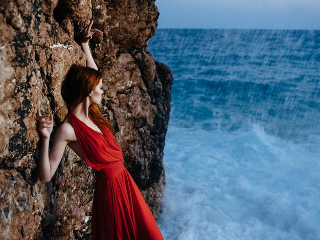 赤いドレスの女性岩石の風景海の波