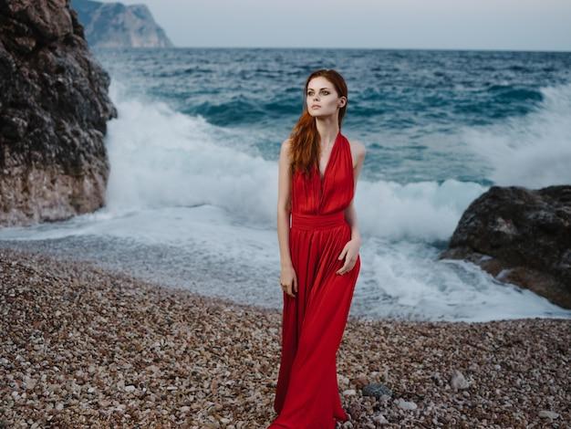 ファッションのシルエットをポーズする赤いドレスの海岸の海の女性