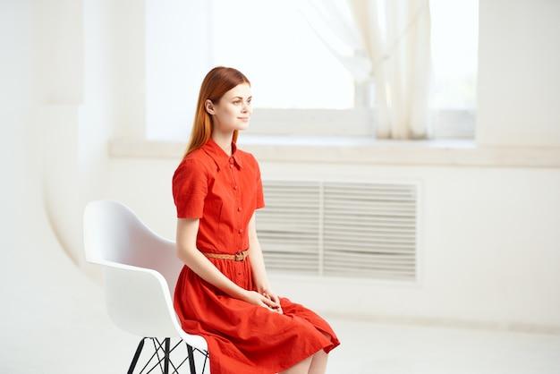 赤いドレスを着た女性が窓のモデルの近くの椅子に座っています