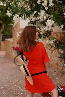 通りを歩いて赤いドレスを着た女性。