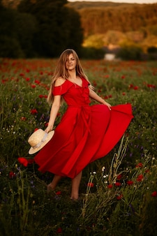 Woman in red dress whirls around on the field with poppies