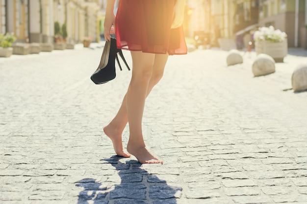 빨간 우아한 드레스를 입은 여성, 하이힐 신발을 손에 들고 맨발로 도시를 걷고 있습니다. 자른 사진을 닫습니다. 태양 광선 광선 샤인 햇살 버스트 샤이니 플레어 효과 글레어 스파클
