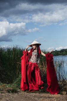 Женщина в красной модной одежде и шляпе в азиатском стиле, стоящая у реки