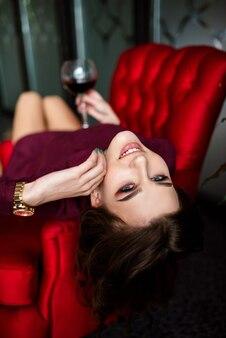 シャンパン グラスを持つ赤いガウンの女性