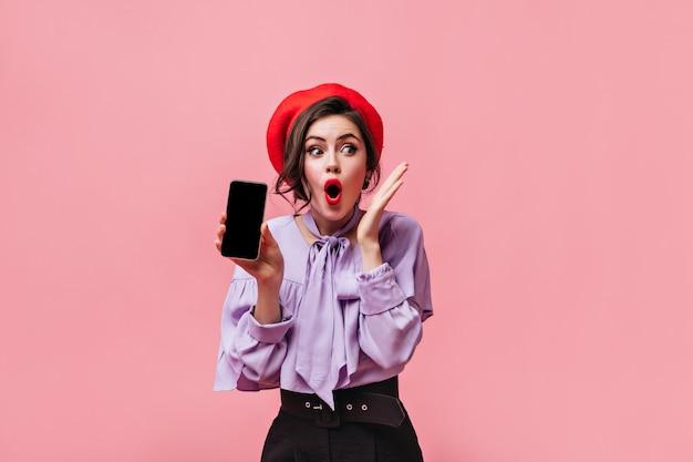 Женщина в красной шляпе и сиреневой блузке держит черный смартфон и в шоке позирует на розовом фоне.