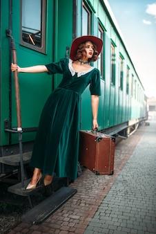 Женщина в красной шляпе на старинном паровозе
