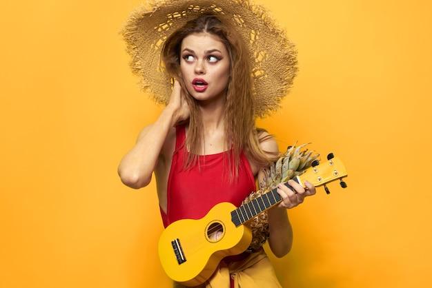 Женщина в красной шляпе укулеле в руках образ жизни летняя красная футболка желтый фон
