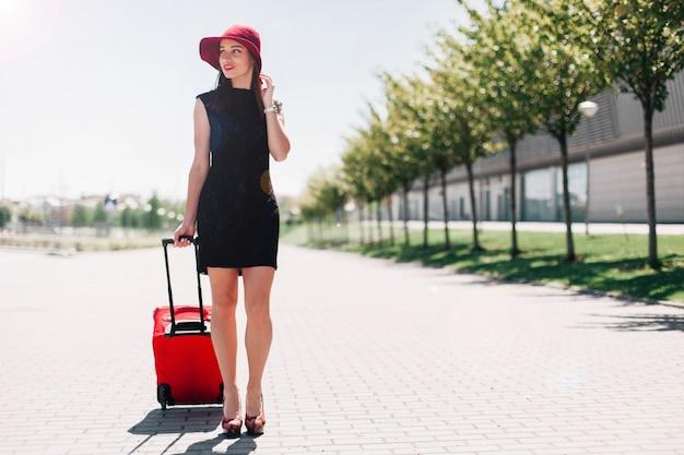 빨간 모자에있는 여자 밖에 빨간 가방으로 걸어