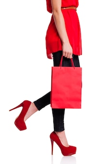 Женщина в красных высоких каблуках держит красную сумку для покупок