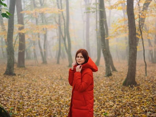 赤いジャケットの女性秋の森の自然散歩ライフスタイル