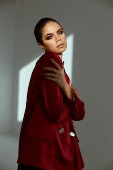 Женщина в красной куртке яркое украшение косметики студия модели
